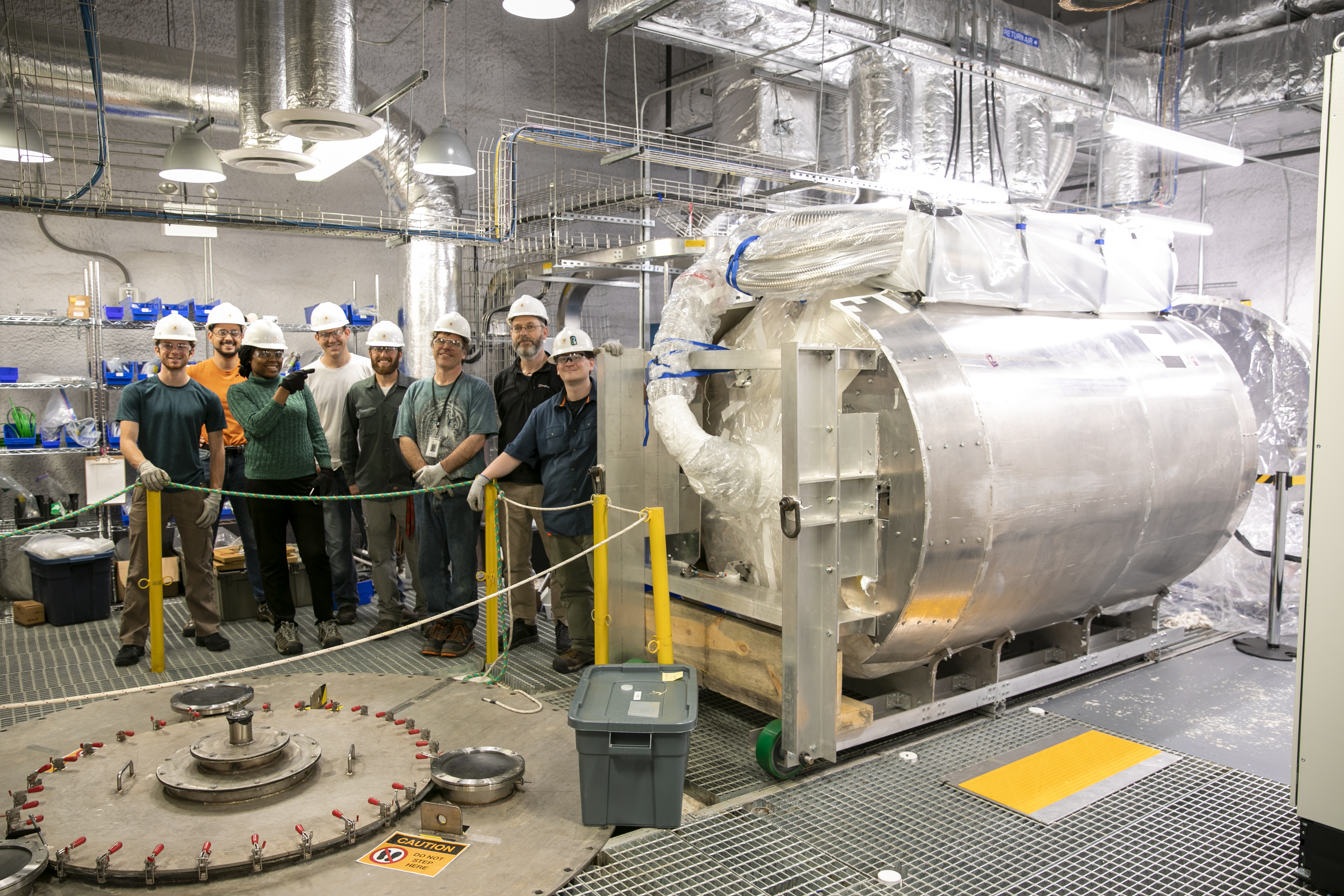 Group of workers stands beside cryostat vessel