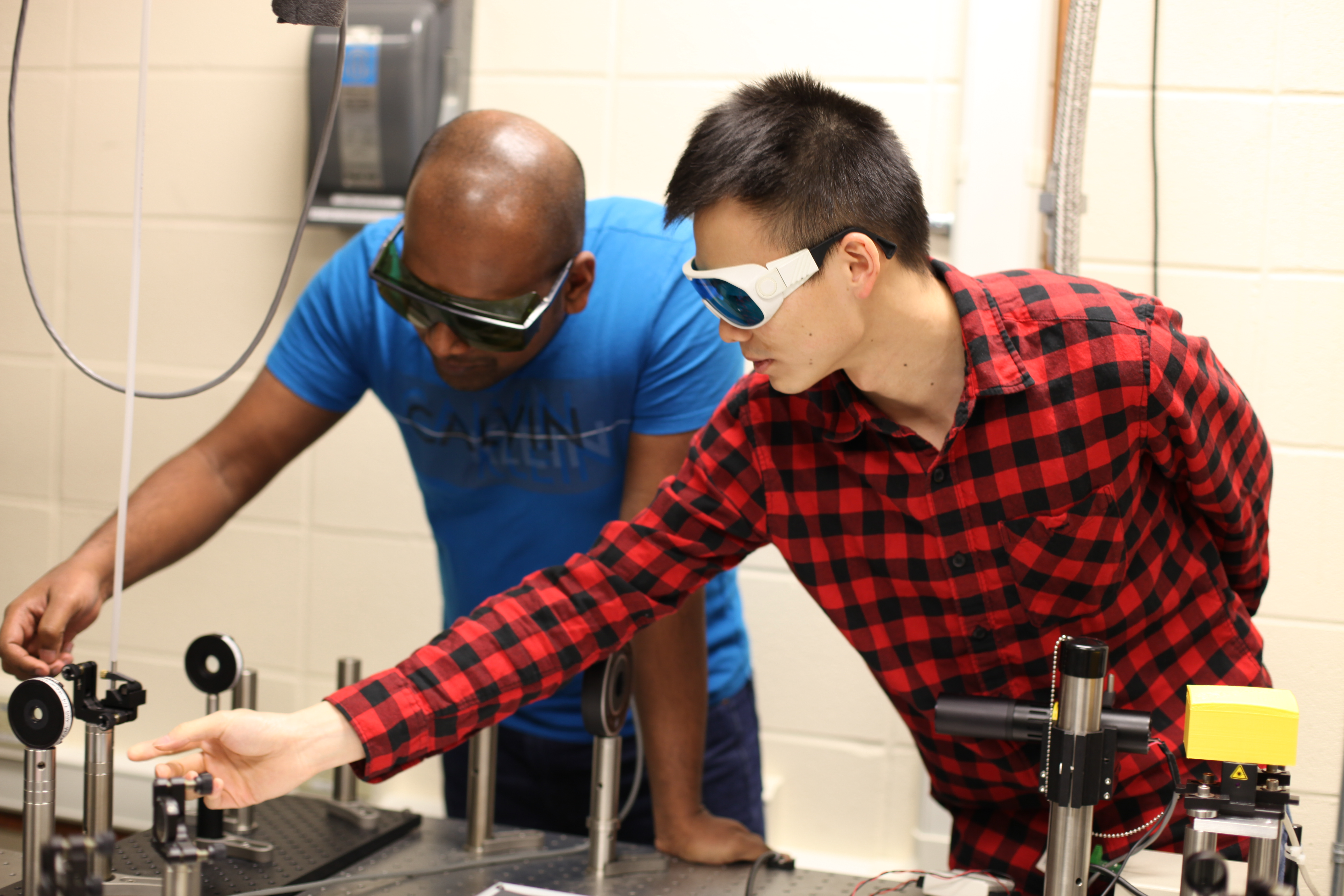 SD Mines students Ishara Ratnayake and Lin Kang work with Smith to develop laser physics technologies.