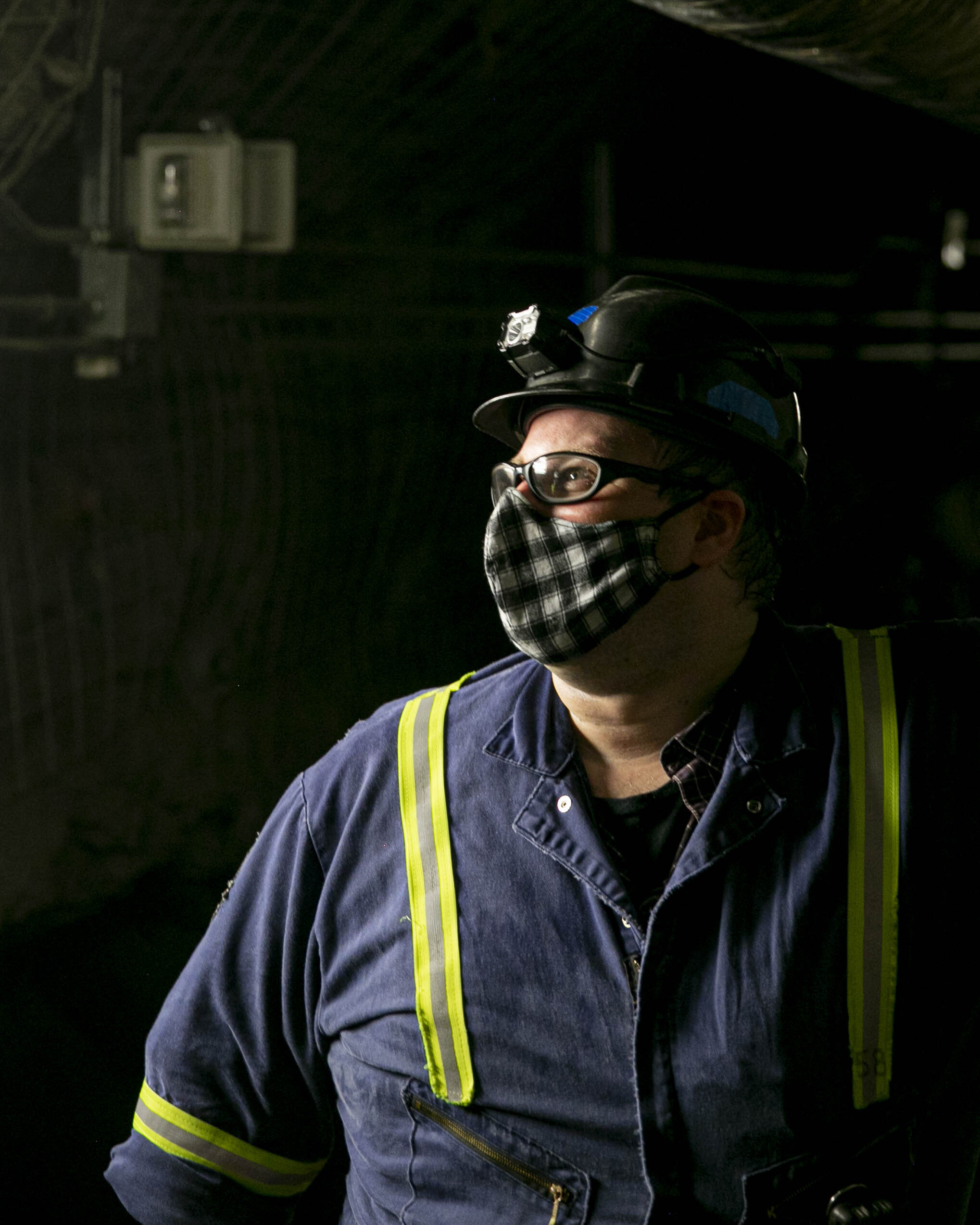 A man wearing a covid-19 mask stands in a dimly lit tunnel