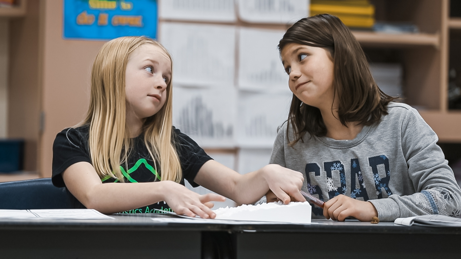 Two female students look inquistivly at each other over a science activity.
