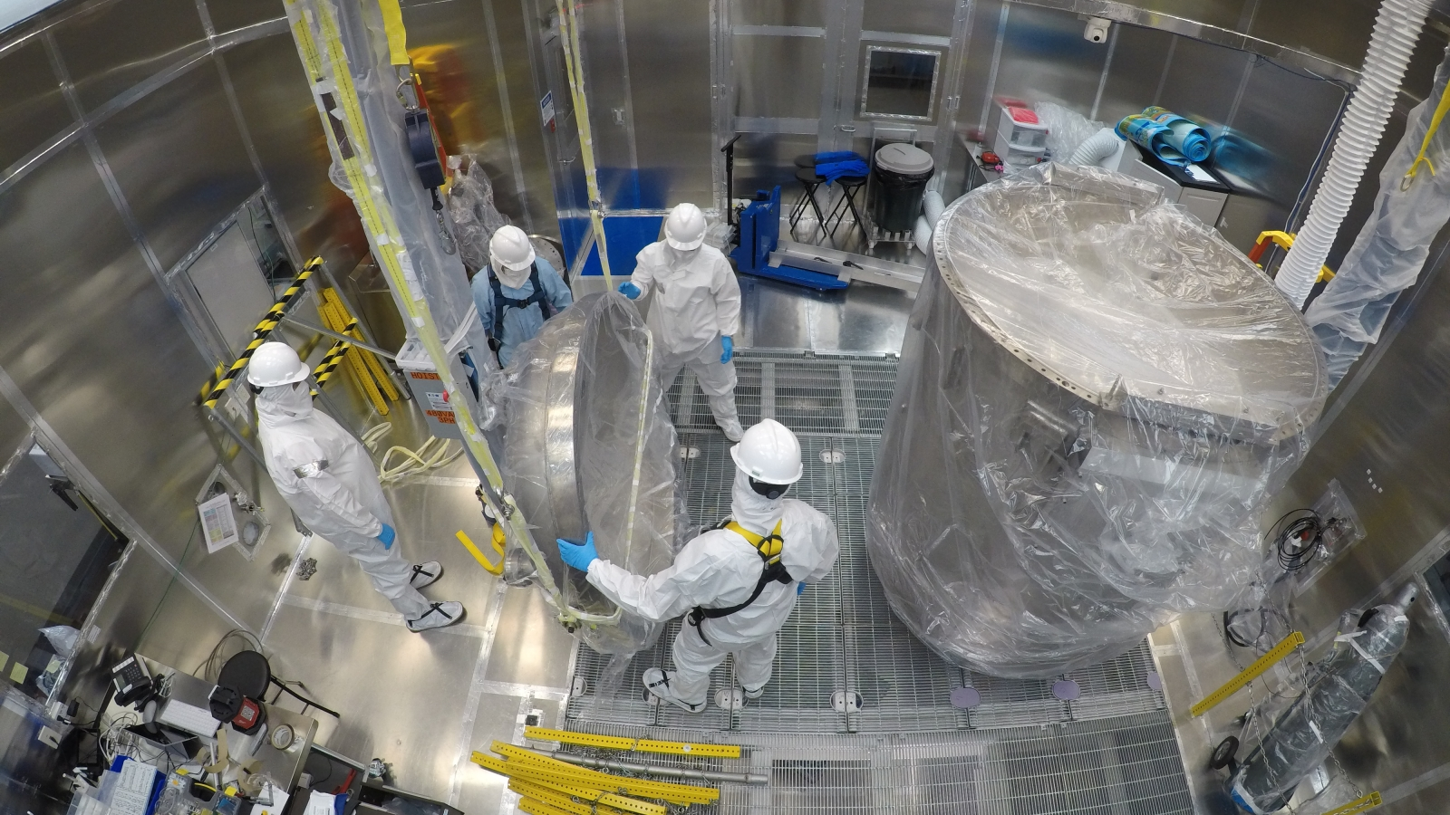 Engineers clean the LUX-ZEPLIN cryostat inside the Surface Lab's Class 1000 clean room in preparation for the next generation search for dark matter.