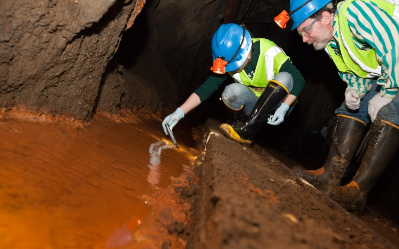 Biologists take samples from an underground pool