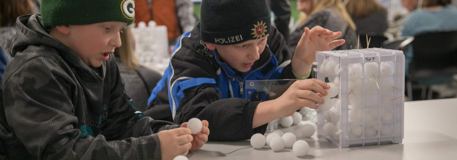 Students participate in a cavern building activity using foam balls and tooth picks as support.